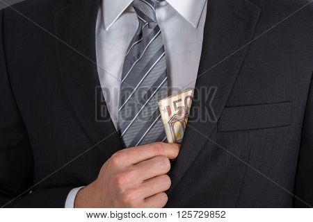 Businessman Putting Bribe Money In Suit Pocket