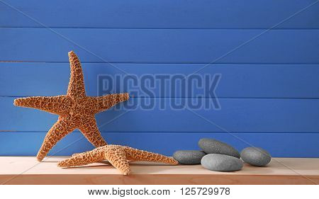 Starfishes with pebbles on blue wooden background