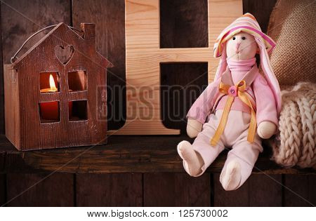 Toy bunny with letter, woolen scarf and house on wooden background
