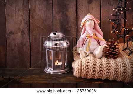 Toy bunny with woolen scarf, garland and lantern on wooden background