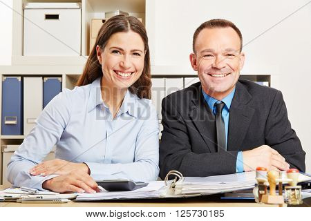 Two smiling business people sitting at the desk in an office