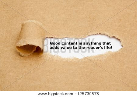 The quote Good content is anything that adds value to the reader's life appearing behind torn brown paper.