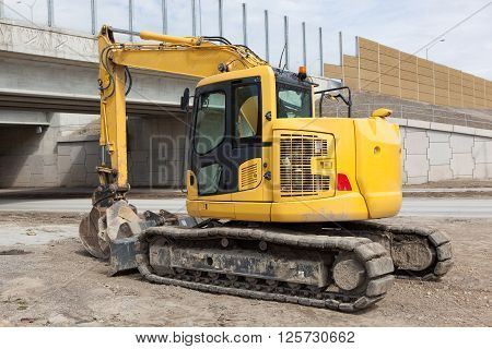 A yellow backhoe parked at a construction site