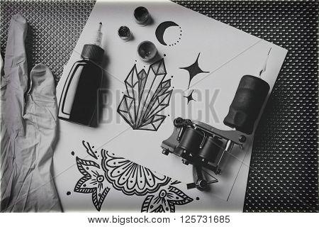 Tattoo machine, sketch and tattoo supplies, close up. Retro stylization