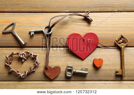 Keys with heart trinkets on wooden background