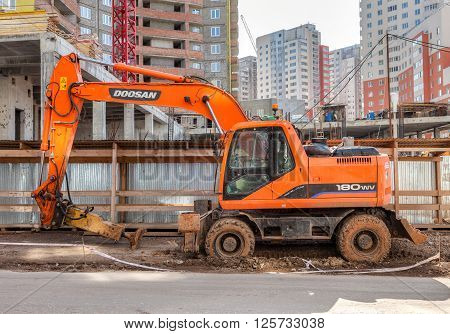 SAMARA RUSSIA - APRIL 10 2016: Construction machinery stands near a apartment buildings under construction