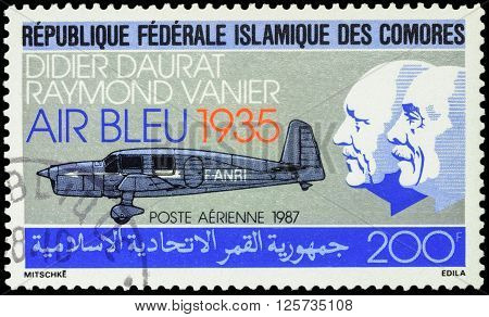 MOSCOW RUSSIA - APRIL 11 2016: A stamp printed in Comoros shows old airplane and portraits of Didier Daurat and Raymond Vanier devoted to the