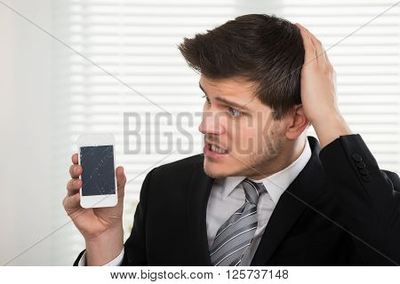 Unhappy Businessman Looking At Broken Mobile Phone