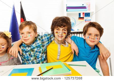 Pupils with flags on their cheeks learning languages sitting at the desk in the classroom