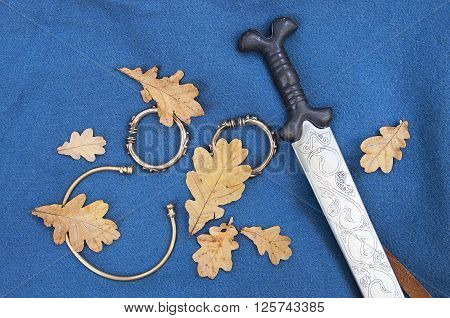 Reconstructed celtic sword with oak leaves on blue background