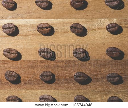 Image of many coffee beans in a pattern on wood