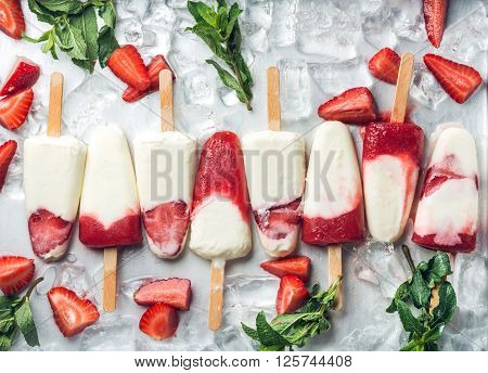 Strawberry yogurt ice cream popsicles with mint over steel tray background. Top view