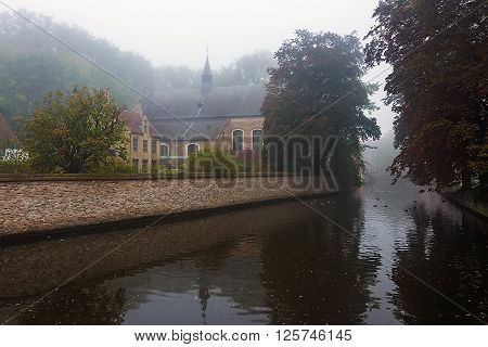 Begijnhof Bruges. Misty autumn morning haze over the water of canal and reflections of trees and ancient belgian houses in Minnerwater park in Brugge
