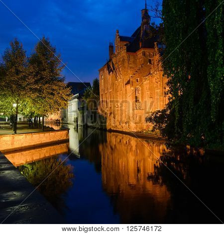Old medieval brick Europe house reflected on the water of canals view in Bruges Belgium. Night scene with illumination and reflections