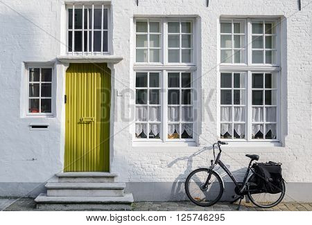 BRUGGE, BELGIUM- 15th SEPTEMBER, 2014. Old brick wall with bright door and leaning bicycle on Brugge street.