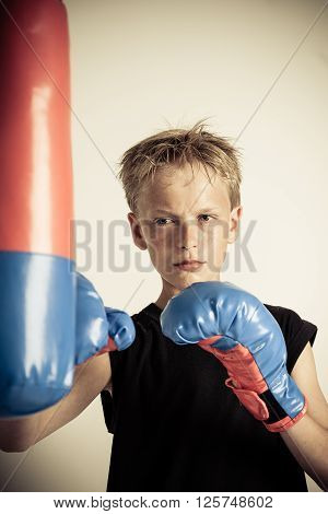 Serious Boy Strikes Punching Bag With Blue Gloves