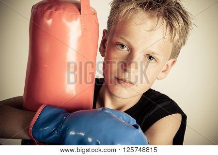 Serious Boy Wearing Black Shirt Hugs Punching Bag