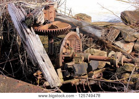 Rusty and broken gears that once controlled water flow of a fast moving river.