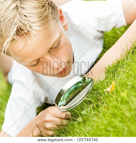 Slanted View Of Boy In White With Magnifying Glass