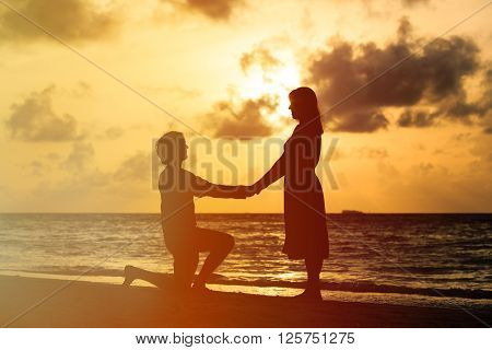 Silhouette of romantic couple at sunset beach, marriage proposal