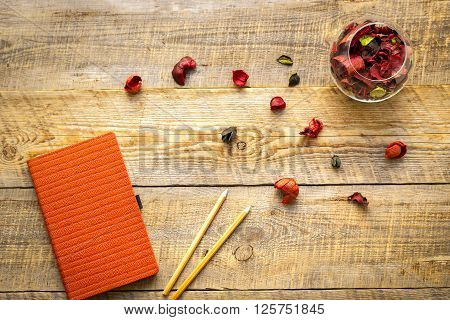 orange notebook with pencil and flower sachets on wooden table - womans working place