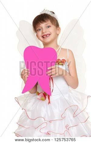 girl child lost tooth fairy dressed in white gown with wings show big tooth shape made from paper