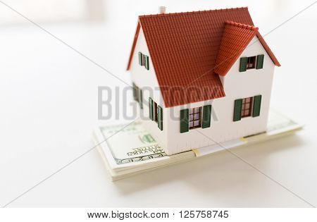 building, mortgage, investment, real estate and property concept - close up of home or house model and money
