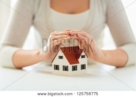 architecture, safety, security, real estate and property concept - close up of hands protecting house or home model