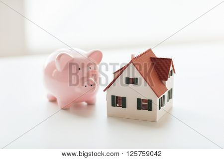 building, mortgage, investment, real estate and property concept - close up of home or house model and piggy bank