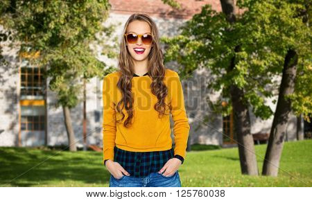people, education, holidays and fashion concept - happy young woman or teen girl in casual clothes and sunglasses over campus and summer park background