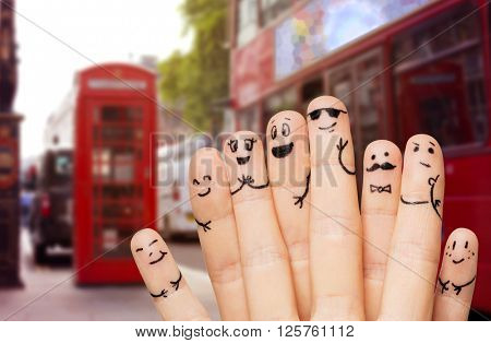 travel, tourism, family, people and body parts concept - close up of two hands showing fingers with smiley faces over london city street and red bus background