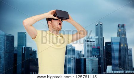 3d technology, virtual reality, entertainment and people concept - happy young man with virtual reality headset or 3d glasses playing game over singapore city skyscrapers background