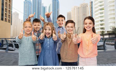 childhood, travel, tourism, gesture and people concept - happy smiling boy and girls showing thumbs up over dubai city street background