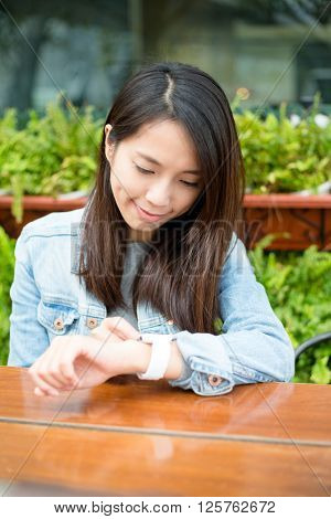 Woman use of smart watch at outdoor cafe