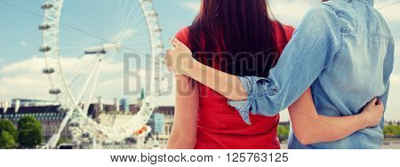 people, homosexuality, same-sex marriage, travel and gay love concept - close up of happy lesbian couple hugging over london ferry wheel background