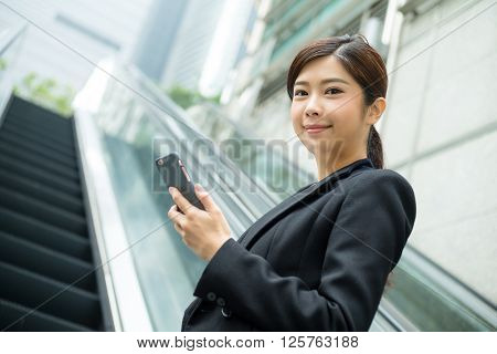 Asian Businesswoman holding a cellphone and standing on escalator