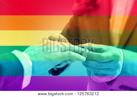 people, homosexuality, same-sex marriage and love concept - close up of happy male gay couple hands putting wedding ring on over rainbow flag stripes background