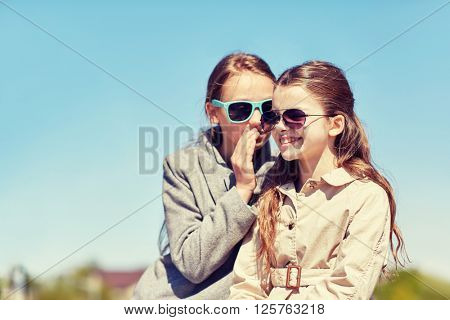 people, children and friendship concept - happy little girl in sunglasses whispering her secret to friends ear or gossiping outdoors