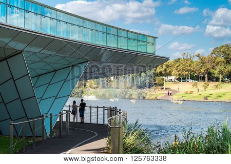 Adelaide Australia - January 3 2016: Young couple enjoying the view while standing under the waterfall from the foot bridge in Elder Park on a bright day