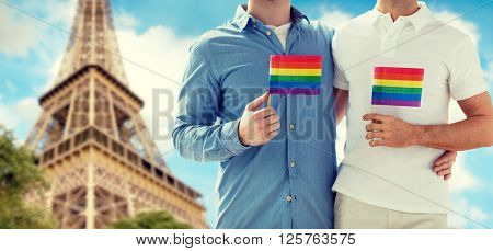 people, homosexuality, same-sex marriage, travel and love concept - close up of happy male gay couple holding rainbow flags and hugging from back over paris eiffel tower background