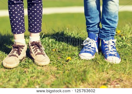 people, children, friends and friendship concept - close up of kids legs in shoes on grass outdoors