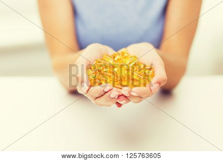 healthy eating, medicine, health care, food supplements and people concept - close up of woman hands holding pills or fish oil capsules at home