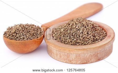 Ajwain seeds in a wooden bowl and spoon over white background