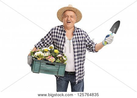 Cheerful mature horticulturist holding a rack of flowers and a small spade isolated on white background