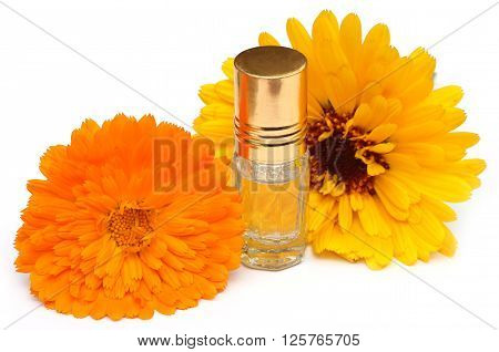 Closeup of calendula with scent bottle over white background