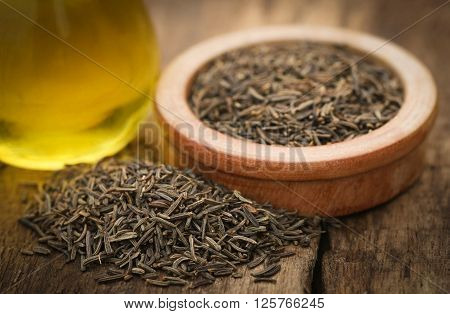 Caraway seeds with essential oil on wooden surface