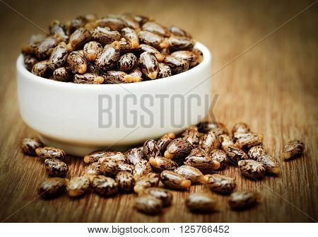 Castor beans in a ceramic bowl on wooden surface ** Note: Shallow depth of field