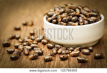 Castor beans in a ceramic bowl on wooden surface