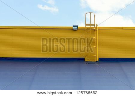part of an industrial structure or warehouse of a hangar with a roof and a ladder closeup against the cloudy sky
