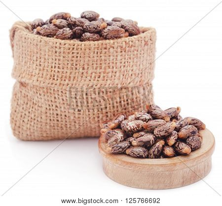Castor beans in bowl and a sack over white background